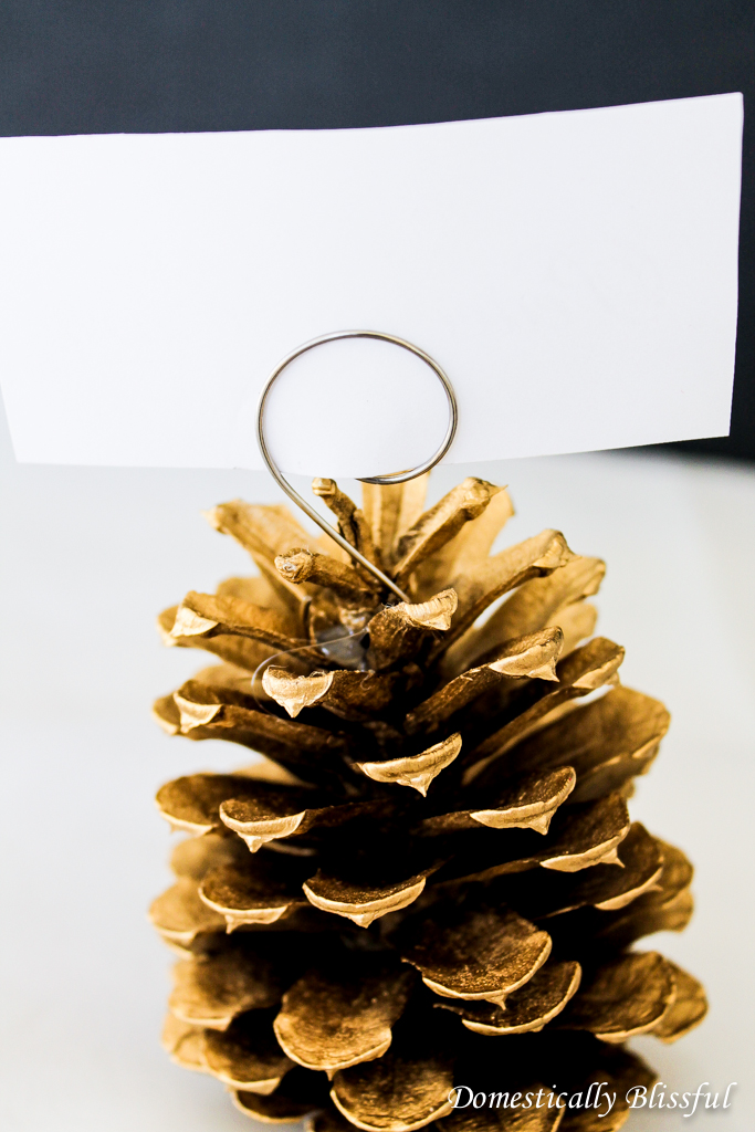 Hot glue ornament hooks to pinecone