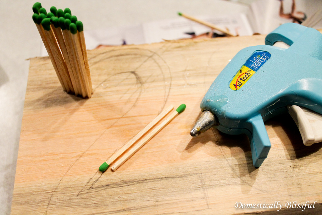Hot glue the matchsticks to the board