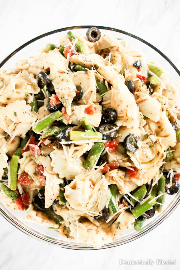 This Pesto Tortellini Salad is filled with asparagus, black olives, artichoke hearts, & sun dried tomato bruschetta making it a flavorful last minute dish for any occasion.