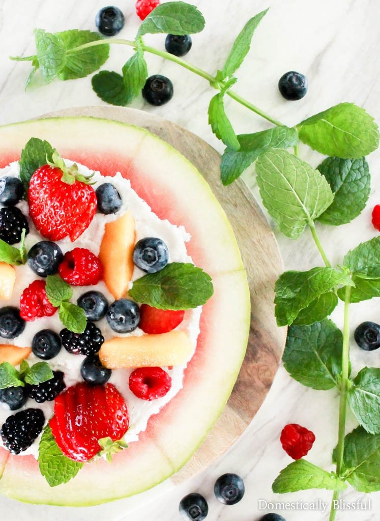 Watermelon Pizza topped with whipped coconut cream & your favorite summer fruit.