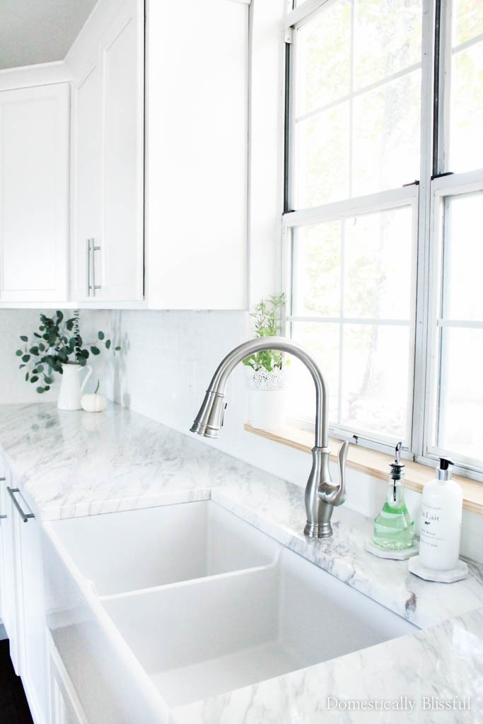 An 80's kitchen remodelcomplete with a rotary phone renovated into an open & dreamy white chef's kitchen with a large marble island.