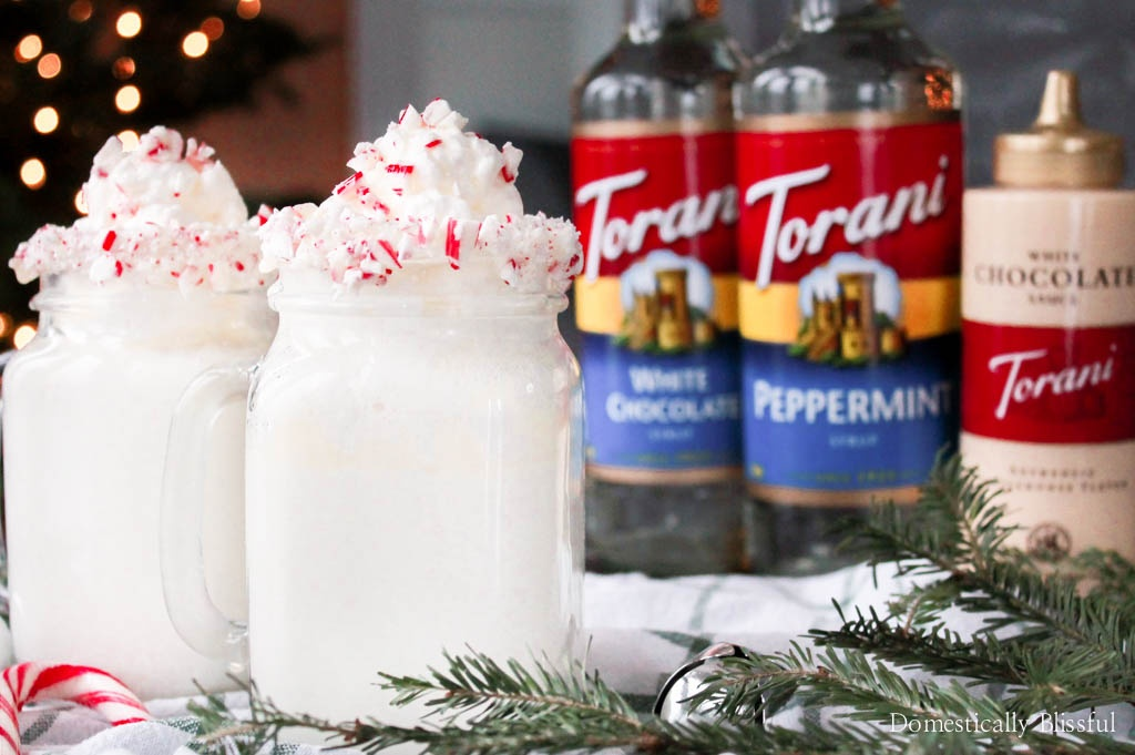 This Peppermint White Hot Chocolate is served in a candy cane rimmed mug & topped with homemade peppermint whipped cream, white chocolate drizzle, & crushed candy cane pieces.