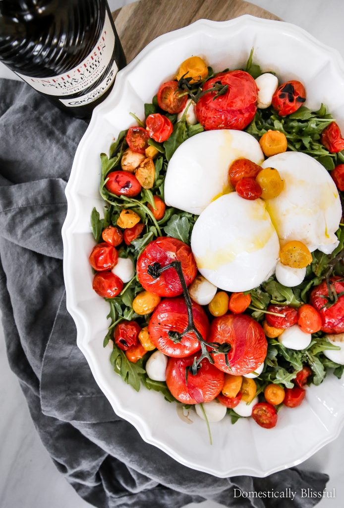 This Roasted Tomato Burrata Caprese Salad looks fancy but is actually incredibly easy to create & tastes delicious as an entree or side dish!