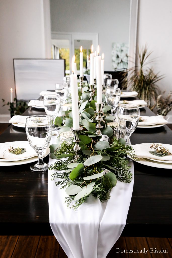 This Silver Bell Tablescape is perfect for the holiday season, with 24 silver bells, tall silver candlesticks, & mercury candle holders tucked into silver dollar eucalyptus that lay upon a white table runner you are sure to have a beautiful holiday party!