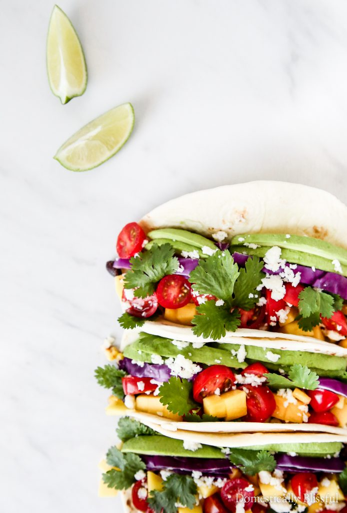 These vegetarian Black Bean Mango Tacos are loaded with fresh ingredients like avocado, red cabbage, & mango!