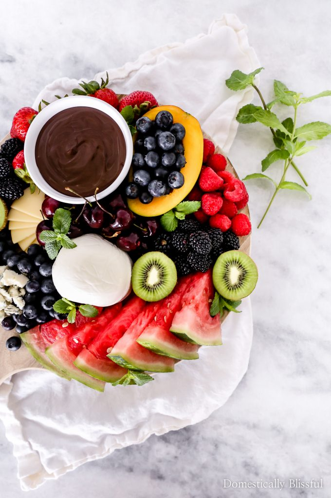 This Summer Fruit Plate is loaded with watermelon, cherries, kiwi, mango, blueberries, raspberries, blackberries, melted dark chocolate, & a variety of delicious cheeses.