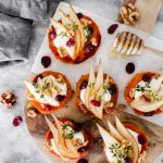 These Pear & Whipped Goat Cheese Sweet Potato Rounds are topped with slices of pear, whipped goat cheese, walnuts, dried cranberries, fresh thyme, and a drizzle of honey.