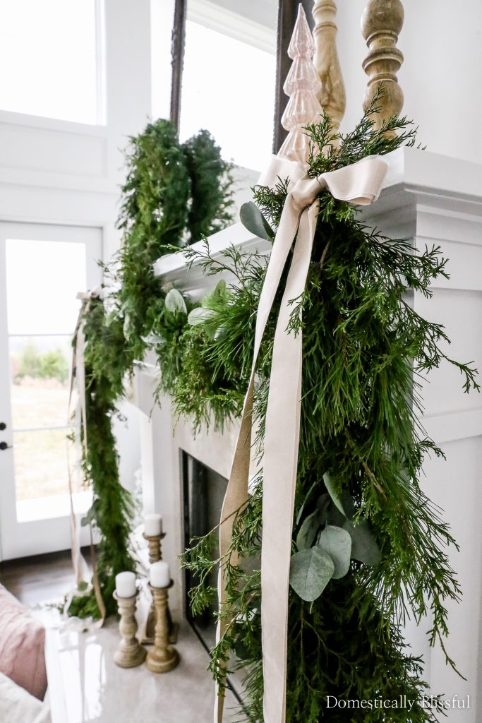 This DIY fresh evergreen garland is inexpensive to create with a mixture of foraged fresh evergreen stems and faux eucalyptus stems topped with two champaign ribbon bows.