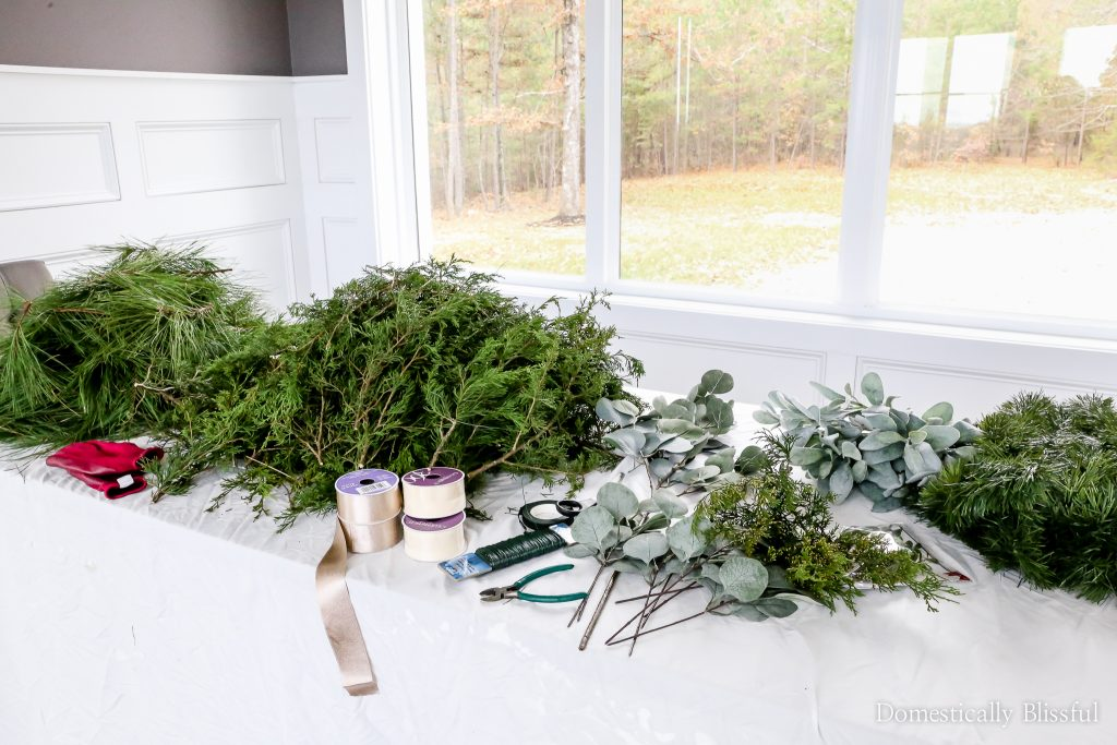 This DIY Christmas garland is inexpensive to create with a mixture of foraged fresh evergreen stems and faux eucalyptus stems topped with two champaign ribbon bows.