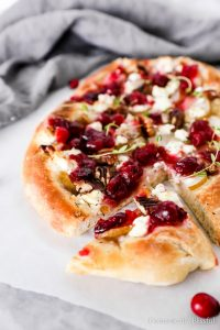 This Cranberry Pear Flatbread is topped with goat cheese, fresh pear, cranberry sauce, and pecans, making it a delicious Thanksgiving leftover recipe.
