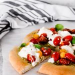This Burrata Caprese Pizza has a pesto base and is topped with broken burrata that melts into the roasted cherry tomatoes.