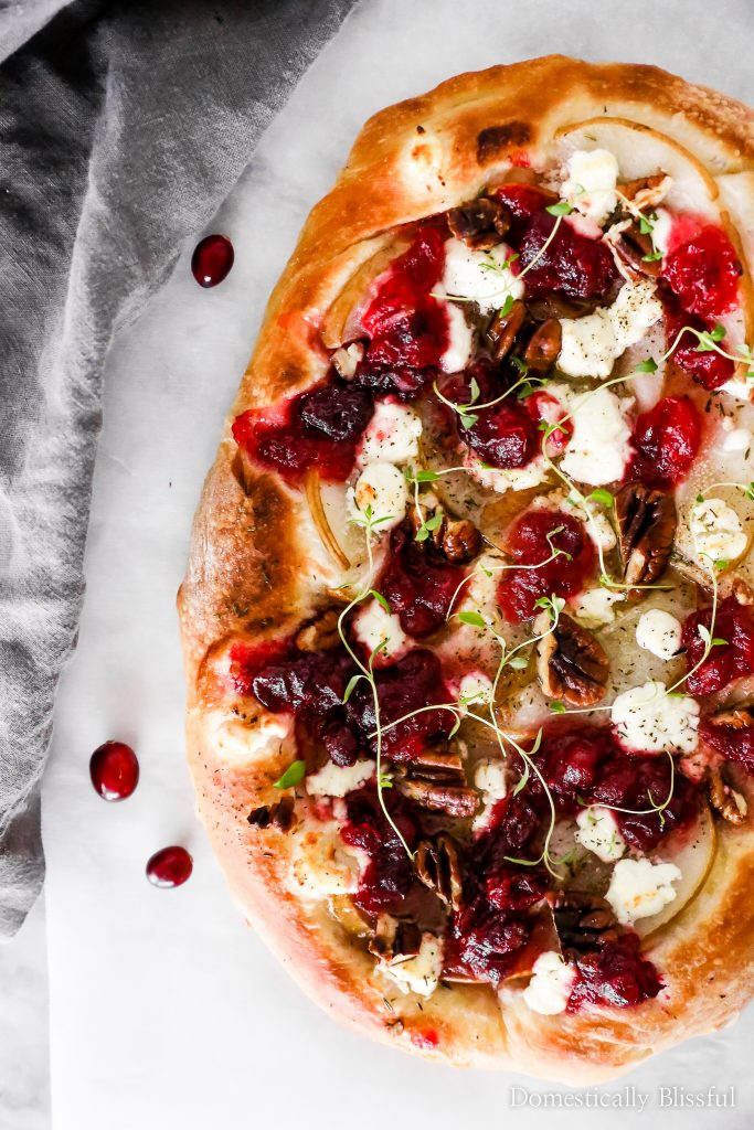 This Cranberry Pear Flatbread is topped with goat cheese, fresh pear, cranberry sauce, and pecans, making it a delicious Christmas appetizer or Thanksgiving leftover recipe.