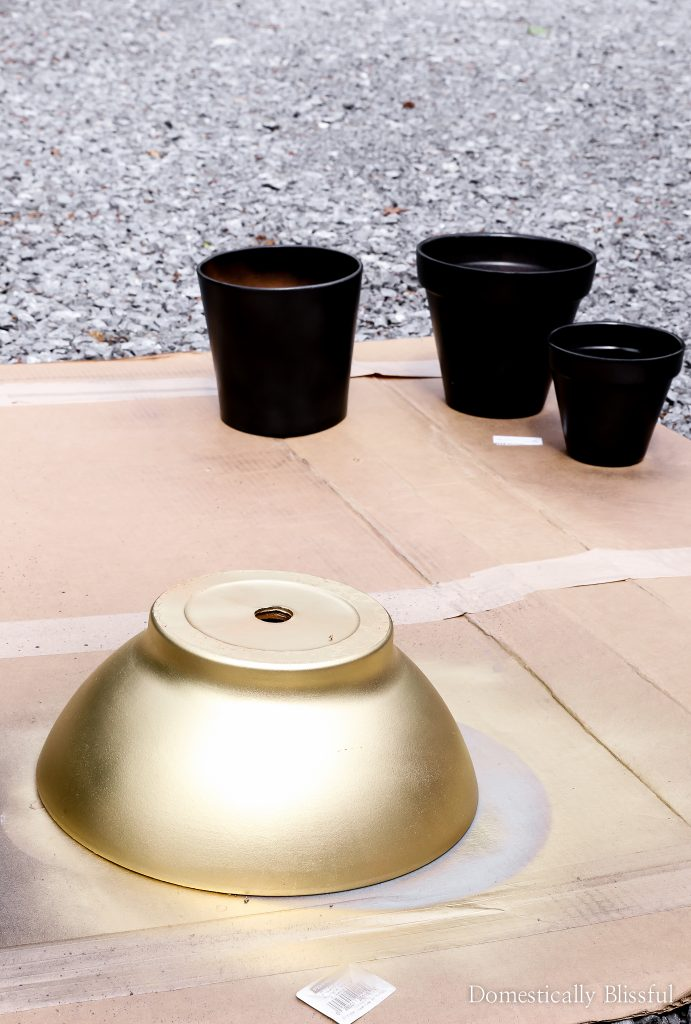 DIY black aged terra cotta pots, with hints of grey and gold coming out from behind the black paint and tips on how to create this aged effect.