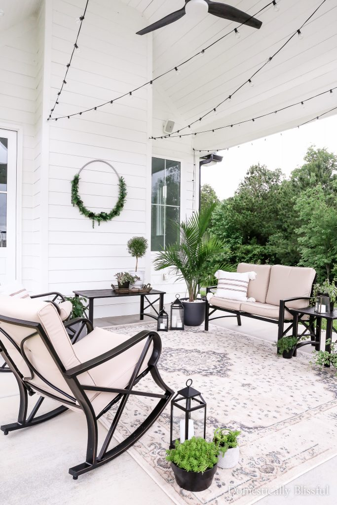 A summer patio reveal with lots of plants, pretty patio decor, an outdoor rug, and twinkle lights.