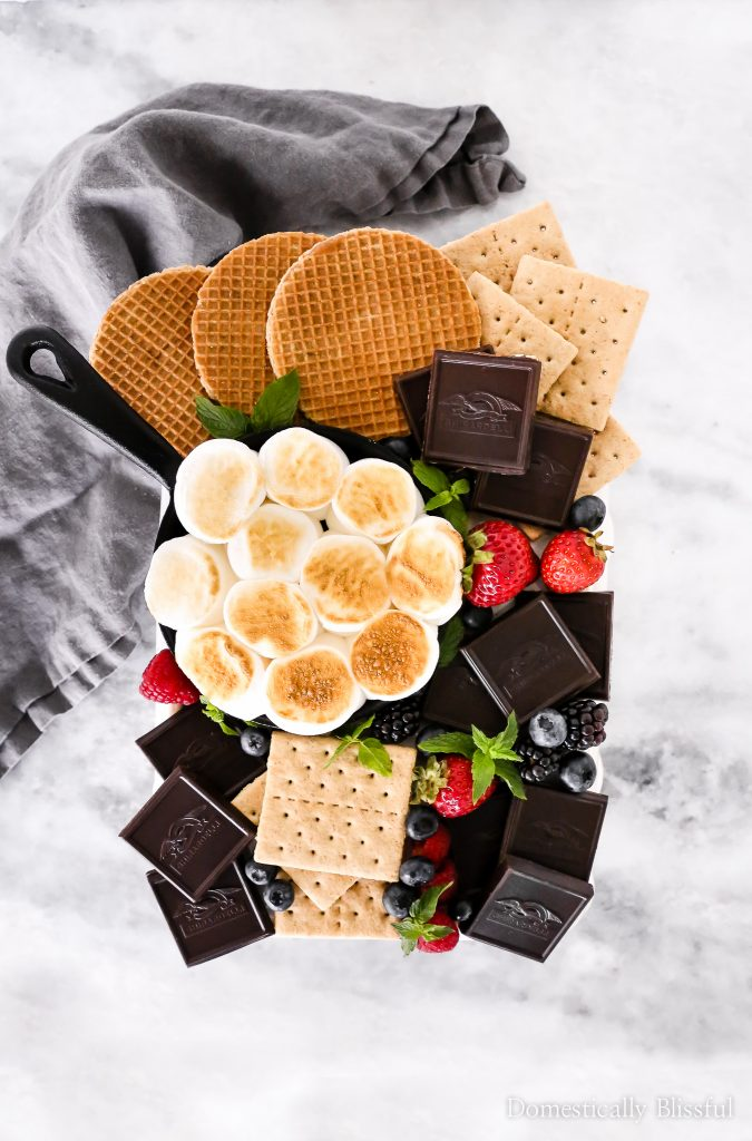 This S'mores Charcuterie Board is covered with fresh berries, toasted marshmallows, graham crackers, wafer cookies, and Ghirardelli Intense Dark Chocolate.